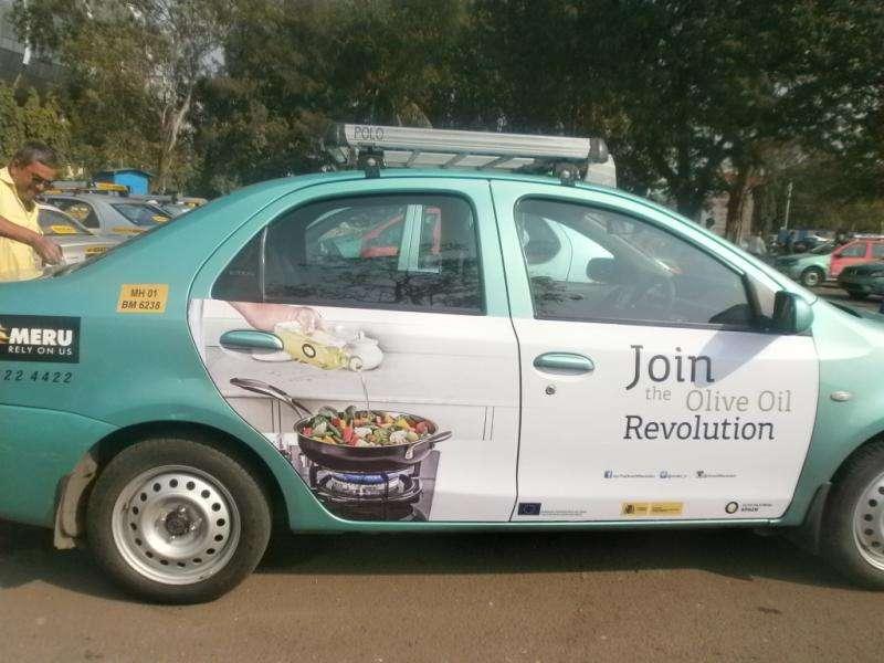 Taxi mit Werbung für Olivenöl aus Spanien